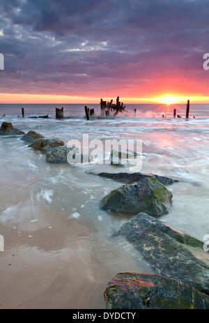 Happisburgh beach and the derelict sea defences at sunrise on the Norfolk coast. - Stock Photo