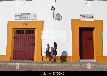 Two young women walk by the Plaza de toros de la Real Maestranza. - Stock Photo