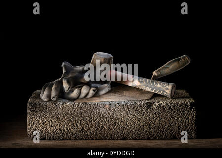 Builder's brick trowel with lump hammer and gloves resting on a concrete block. - Stock Photo