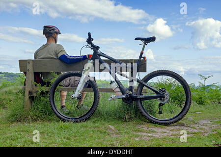 Male mountain biker resting on a wooden bench. - Stock Photo