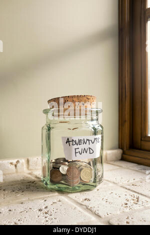 Glass jar labelled Adventure Fund containing loose change. - Stock Photo