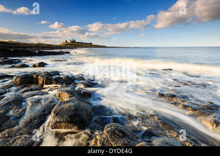 Dunstanburgh Castle from the shore in late afternoon light. - Stock Photo