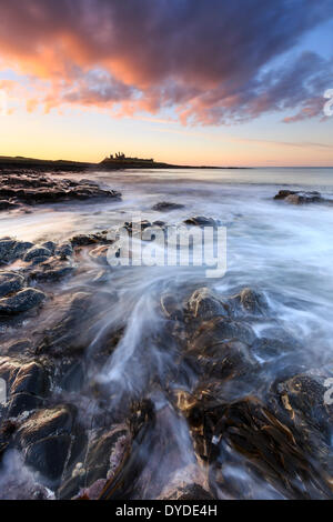 Sunset over Dunstanburgh Castle with waves breaking over the rocks in the foreground. - Stock Photo