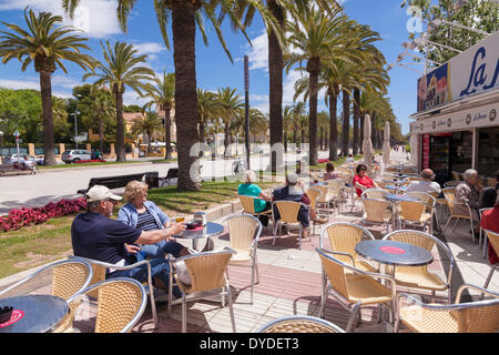 Tourists enjoying the sun at a street cafe on Salou promenade. - Stock Photo