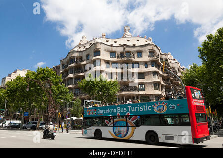 Open top tourist bus passing La Pedrera in Barcelona. - Stock Photo