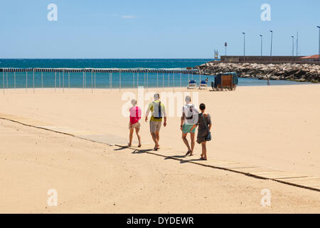 Four people walking down slatted wood access ramp to beach at Cambrils in Spain. - Stock Photo