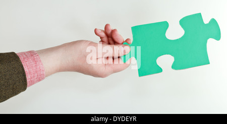 green puzzle piece in male hand on grey background - Stock Photo