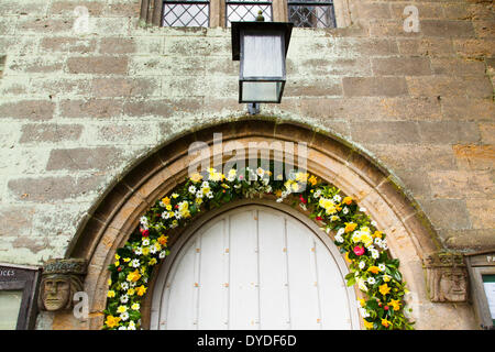 Porch light and flowers surrounding the entrance to Tillington Church in West Sussex. - Stock Photo