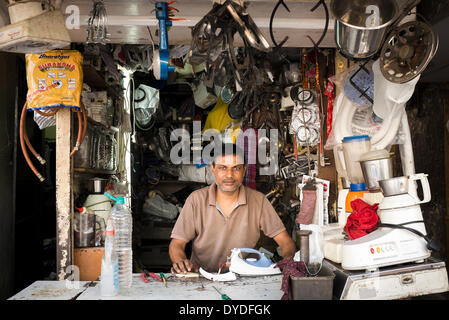 A man behind the counter of his shop specialising in repairs of gas and electrical kitchen appliances. - Stock Photo