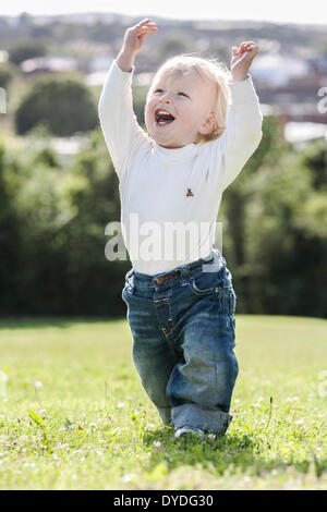 18 month old baby boy very happy on a hill. - Stock Photo