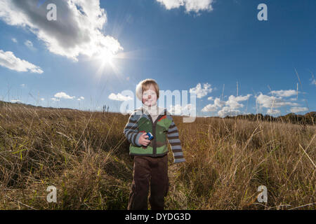 A two year old boy running in the countryside on a sunny day.