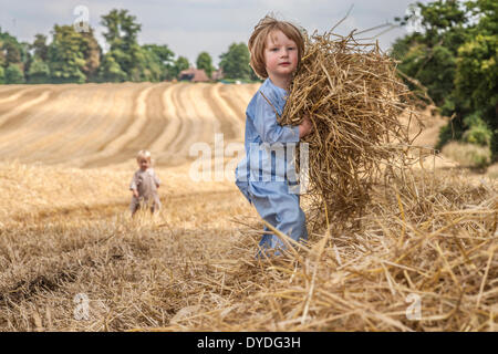 A two year old boy running in a field collecting straw.