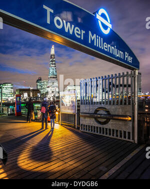 People looking up at The Shard at night from the Tower Millennium Pier. - Stock Photo