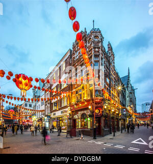 Decorations for Chinese New Year in Wardour Street in London at dusk. - Stock Photo