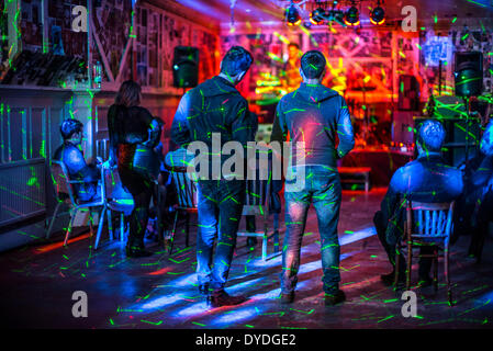 Watching a live performance in a small bar. - Stock Photo