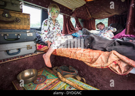 Two boys having fun in a VW camper van  at a festival. - Stock Photo