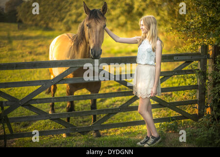 A 15 year old girl with a horse. - Stock Photo