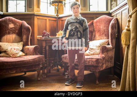 A young boy standing with a book under his arm in Thornbury Castle. - Stock Photo