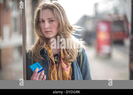 A young woman holds an Oyster card at a London bus stop. - Stock Photo