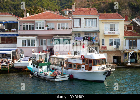 Turkish homes and boats on the Bosphorus Strait, Istanbul in Turkey. - Stock Photo