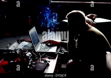 Berlin, Germany. 09th Apr, 2014. A man smokes while working on his laptop next to a professional camera in Berlin, - Stock Photo