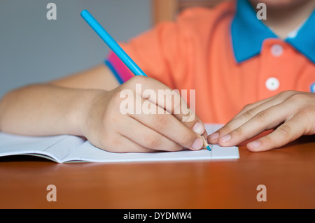 Boy Student Doing Work at School Desk - Stock Photo
