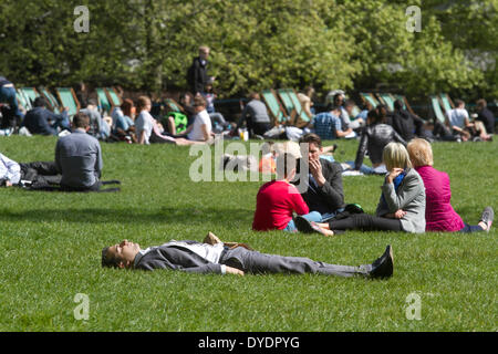 London UK. 15th April 2014. An office workers enjoy the sunshine during a lunch break in Green Park on a spring - Stock Photo