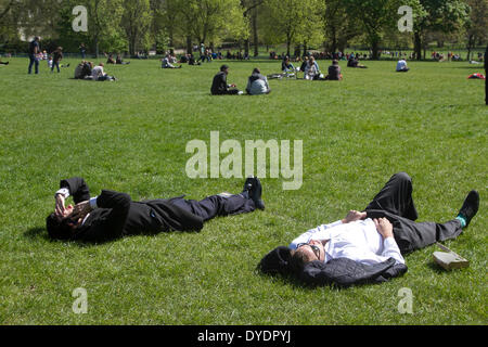London UK. 15th April 2014.  Office workers enjoy the sunshine during a lunch break in Green Park on a spring day - Stock Photo
