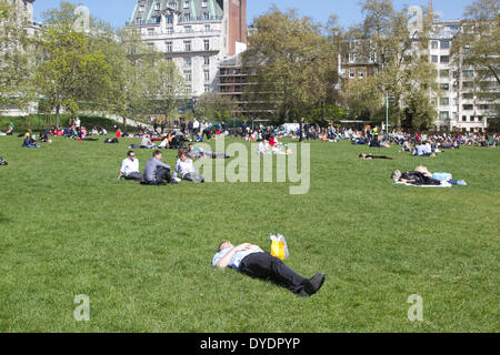 London UK. 15th April 2014. An office worker enjoys the sunshine during a lunch break in Green Park on a spring - Stock Photo