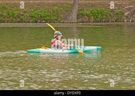 Woman wearing personal floatation device PFD paddling kayak in river - Stock Photo