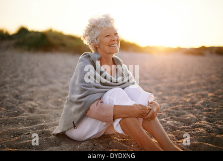 Happy retired woman wearing shawl sitting relaxed on sand at the beach. Senior caucasian woman sitting on the beach - Stock Photo