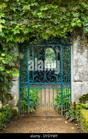 English Garden With Ornate Wrought Iron Gate Covered With