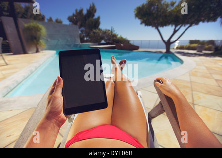 Young woman relaxing on a lounge chair using a tablet PC near the pool. User POV. Female model sitting on a deckchair. - Stock Photo
