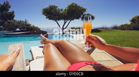 Young lady in bikini holding orange juice glass while sitting on a lounge chair along the poolside on a sunny day. - Stock Photo