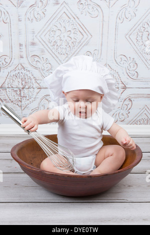 A Six Month Old Baby Boy Dressed as a Chef While Sitting in a Large Bowl Holding a Whisk - Stock Photo