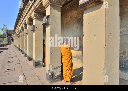 Visiting monks in yellow strolling among the bas-relief scenes from the Hindu period in the main entrance of Angkor - Stock Photo