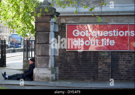 A man sits on the pavement by a sign 'Got questions about life' in West London's affluent Knightsbridge. - Stock Photo