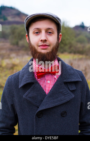 Trendy hipster guy outdoors in the winter in a fashion portrait of the handsome man. - Stock Photo