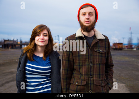Modern, trendy, hipster couple in an abandoned train yard at dusk in this fashion style portrait. - Stock Photo