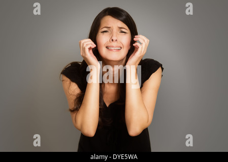 Distraught tearful young woman with her hands clasped in anguish standing with downcast eyes against a white studio - Stock Photo