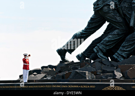 US Marine Corps Staff Sgt. Codie Williams plays the bugle near the giant feet of the Marine Corps War Memorial during - Stock Photo