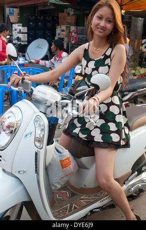Young woman on motorcycle near the market in Kratie, Cambodia - Stock Photo