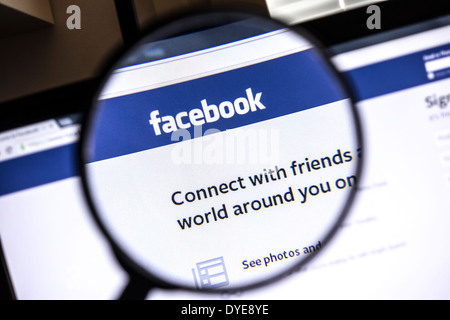 Facebook website zoomed in under a magnifying glass - Stock Photo