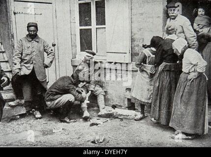 World War 1 - A major nursing a wounded German as villagers look with curiosity 1915 - Stock Photo