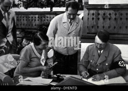 Adolf Hitler 1889-1945. German politician and the leader of the Nazi Party signs state documents watched by a secretary - Stock Photo