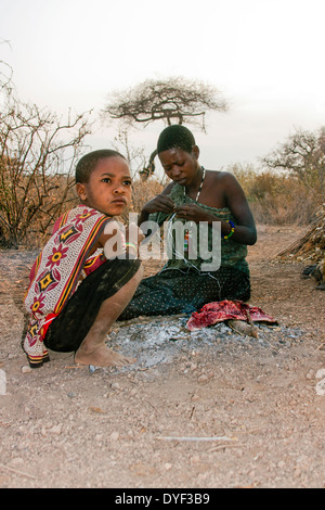 Hadzabe woman and Child, drying meat on a fire. Photographed in Tanzania, Lake Eyasi - Stock Photo