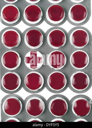 PACKETS OF RED THROAT LOZENGES WITH ONE AS A CROSS - Stock Photo
