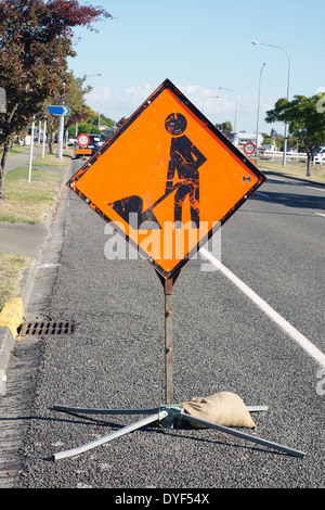 Road works sign used to warn drivers of construction ahead in urban New Zealand - Stock Photo