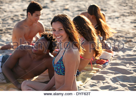 Friends relaxing on beach blanket together - Stock Photo