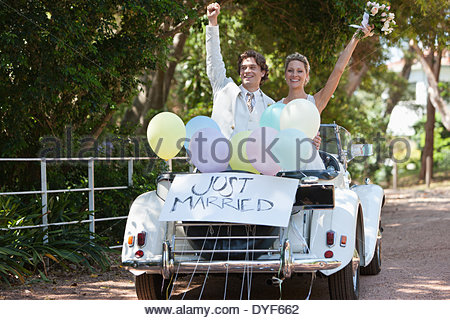 Bride and groom riding in convertible - Stock Photo